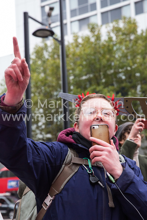 London, UK. 30th October, 2018. Mags Dewhurst, Vice-President of the Independent Workers of Great Britain (IWGB) trade union, addresses members and supporters marching together with other precarious workers from the offices of Transport for London to the University of London via the Court of Appeal in support of Uber drivers who are seeking employment rights. The Court of Appeal will today hear an appeal by Uber against a ruling that its drivers are employees rather than self-employed workers.