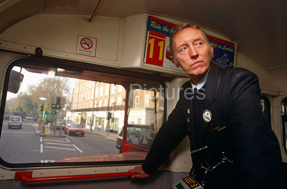 Before they were all replaced as working modes of public transport, a conductor is seen while travelling along a London road, as part of a two-man crew of a number 11 red London bus, England UK. The bus is a traditional design called a Routemaster which has been in service on the capital's roads since 1954 and is nowadays only seen on heritage and tourist routes. From any angle, the bus is easily recognisable as that classic British transport icon. The conductor is the last human link with friendly public travel in London. He is usually a friendly face to accompany unsure travellers, often helping them reach their stop and answering questions about the journey with good humour and kindness. Their removal in favour of single driver crews meant that bus travel became more intimidating.