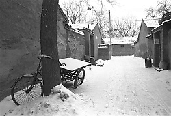 Tricycle parked in an old Beijing hutong during winter snow