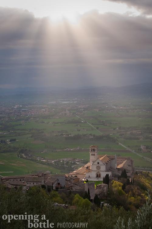 The sun sets over Basilica di San Francesco (Church of St. Francis), Assisi, Umbria, Italy.