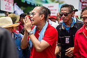 06 APRIL 2014 - BANGKOK, THAILAND:  NATTAWUT SAIKUA, a Red Shirt core leader, offers a wai, or traditional Thai greeting as he walks through the crowd at a Red Shirt rally in a Bangkok suburb Sunday. Red Shirts and supporters of the government of Yingluck Shinawatra, the Prime Minister of Thailand, gathered in a suburb of Bangkok this weekend to show support for the government. The Thai government is dealing with ongoing protests led by anti-government activists. Legal challenges filed by critics of the government could bring the government down as soon as the end of April. The Red Shirt rally this weekend was to show support for the government, which public opinion polls show still has the support of most of the electorate.  PHOTO BY JACK KURTZ