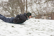 Londoners enjoy sledging on for sale signs at Primrose Hill following a second day of snow on the 1st March 2018 in North London, United Kingdom. A cold front from Russia brings snow and freezing conditions across the UK, dubbed the 'Beast from the East'.