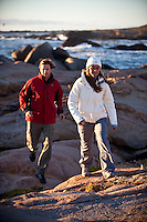Athletic couple training together in out door mountain with ocean in background. woman running with man behind her. Sports people wearing sportswear