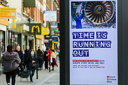 © Licensed to London News Pictures. 19/10/2020. London, UK. Shoppers in north London walk past the government's publicity campaign 'TIME IS RUNNING OUT' for firms that trade with Europe to prepare for a no-deal Brexit. HMRC will contact over 200,000 firms that trade with the EU to set out the new customs and tax rules and how to deal with them. Photo credit: Dinendra Haria/LNP