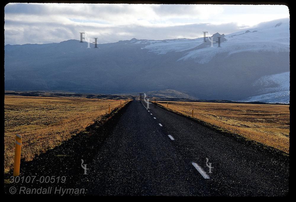 Golden grasses of outwash floodplain frame main highway near Skeidararjokull glacier near Skaftafell National Park; Iceland.