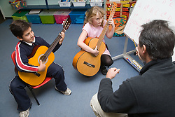 Two primary school children learning to play the guitar in an after school club music lesson,