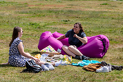 © Licensed to London News Pictures. 25/05/2020. London, UK. Two friends enjoy a picnic on Wimbledon Common with the benefit of a blow up sofa for comfort as members of the public go out in the Bank Holiday sunshine. Weather experts have predict another warm week ahead with highs of 25c. Government is easing the laws on lockdown to let people spend more time outside to enjoy sunbathing and picnicking. Photo credit: Alex Lentati/LNP
