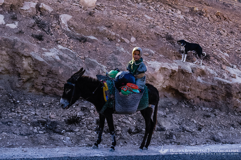 Small girl riding a donkey along the road between Essaouira and Agadir, Morocco.