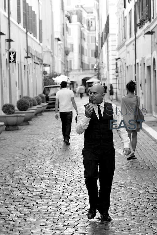 ROME, ITALY - AUGUST 07: A waiter walks in the shopping district on August 7, 2012, in Rome, Italy. Rome, the capital of Italy, was legendarily founded in 753 BC. Successively the capital city of the Roman Kingdom, the Roman Republic and the Roman Empire, Rome is regarded as one of the birthplaces of Western civilization. (Photo by Lucas Schifres/Getty Images)
