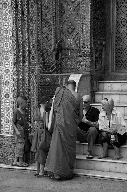 A family of Monks comparing tattoos with a tourist.