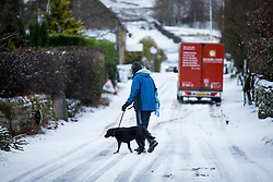 © Licensed to London News Pictures. 13/01/2017. Chesterfield, UK. A man walks his dog through the snow near Curbar Gap, Derbyshire. Snowy and icy weather has resulted in some road closures in rural Derbyshire. Last night saw many parts of the UK covered in snow. Photo credit : Tom Nicholson/LNP