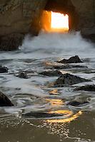 The sun sets through a window to the Pacific,  Big Sur Coast, Pfeiffer State Beach CA, USA.
