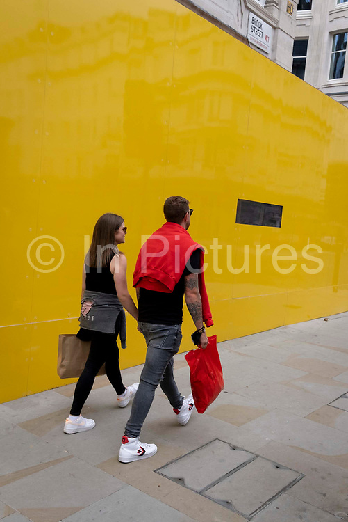 A couple walk hand-in-hand alongside a yellow construction hoarding on Brook Street in Mayfair, on 12th July 2021, in London, England.