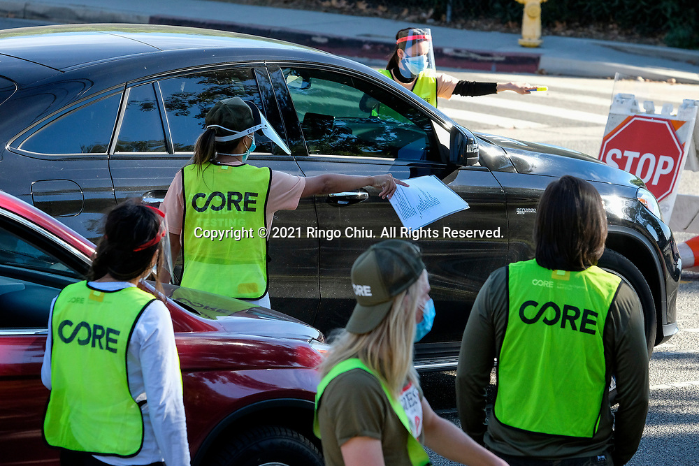 Workers direct traffic as motorists wait in lines to get the coronavirus (COVID-19) vaccine in a parking lot at Dodger Stadium, Friday, Jan. 15, 2021, in Los Angeles. Dodger Stadium reopened Friday as a mass COVID-19 vaccination site, which Mayor Eric Garcetti says will have the capacity to vaccinate 12,000 people a day once it is fully operational.