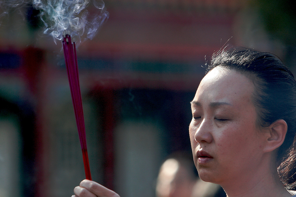 A women offers incense at the front of Baiyuguan.  Baiyuguan,called White Cloud Temple in English, is over 1,200 years old and stands the south west of Beijing, China.  White Cloud Temple is the largest Daoist structure in Beijing and home of the Dragon Gate sect of Daoism.
