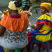 Planquera in tradtiional Caribbean garb offering fresh tropical fruit for sale Cartagena, Colombia.