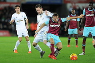 Gylfi Sigurdsson of Swansea city (l) challenges Mark Noble of West Ham Utd. Barclays Premier league match, Swansea city v West Ham Utd at the Liberty Stadium in Swansea, South Wales  on Sunday 20th December 2015.<br /> pic by  Andrew Orchard, Andrew Orchard sports photography.
