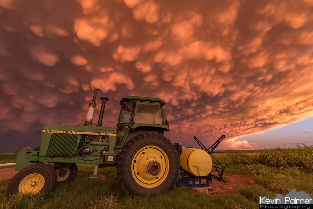 Mammatus clouds are a common sight while storm chasing, but never have I seen them in a sunset like this. They seemed to become more defined and filled nearly the entire sky as the sun sank lower. The fiery colors were so intense that I had to cut back on the saturation. A strong MCS (mesoscale convective system) had moved off to the east as I was passing through Wheatland on my way home. When I noticed this sunset developing I searched for something nearby to serve as a foreground and this old tractor did the trick. Mammatus clouds usually form beneath the anvil of a strong thunderstorm, which means they can be either ahead of or behind the storm. The lobes are about 500m wide on average and show a sinking motion, making it look like the sky is falling. Pilots typically give mammatus a wide berth because of the turbulence they bring. Even though they happen frequently, their formation is not very well understood.