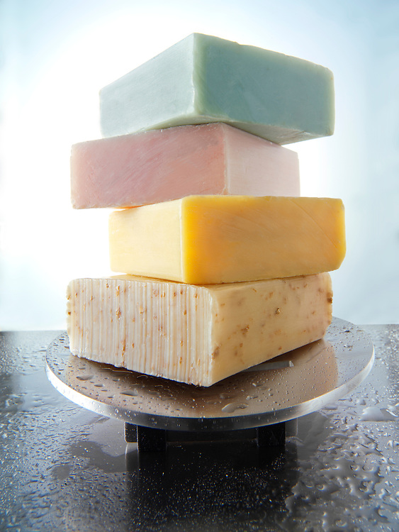 4 bars of scented hand made soap piled on an aluminium soap dish with water droplets