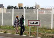 Men walk through 'the Jungle' migrant camp in Calais, France, August 10, 2015. The Calais jungle is the nickname given to a series of camps in the vicinity of Calais, France, where migrants live while they attempt to enter the United Kingdom illegally by stowing away on lorries, ferries, cars, or trains travelling through the Port of Calais or the Eurotunnel Calais Terminal. The migrants are a mix of refugees, asylum seekers and economic migrants from Darfur, Afghanistan, Syria, Iraq, Eritrea and other troubled areas of the world.