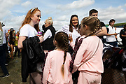 A young girl with red hair talks with two other girls in matching clothes on the fair ground at Appleby Horse Fair, the biggest gathering of Gypsies and travellers in Europe, on 14th August, 2021 in Appleby, United Kingdom. Appleby Horse Fair attracts thousands from Gypsy, Romany, and traveller communities annually, making it the biggest gathering of its kind in Europe. Generally held for a week every June, the fair was postponed in 2020 and pushed forward to August in 2021 due to Coronavirus.
