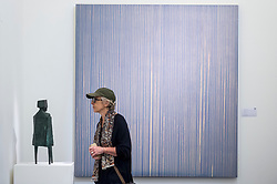 "© Licensed to London News Pictures. 16/11/2018. LONDON, UK. A visitor views ""Conjunction XII"", 1970, by Lynne Chadwick (Est. GBP50,000-80,000) in front of ""Repetition (Grey/Violet)"", 1995, by Callum Innes (Est. GBP12,000-18,000).  Preview of Sotheby's autumn sale of Modern & Post War British art.  Works from the British art scene of the past century will be offered for sale on 20 and 21 November 2018 at Sotheby's in London.  Photo credit: Stephen Chung/LNP"