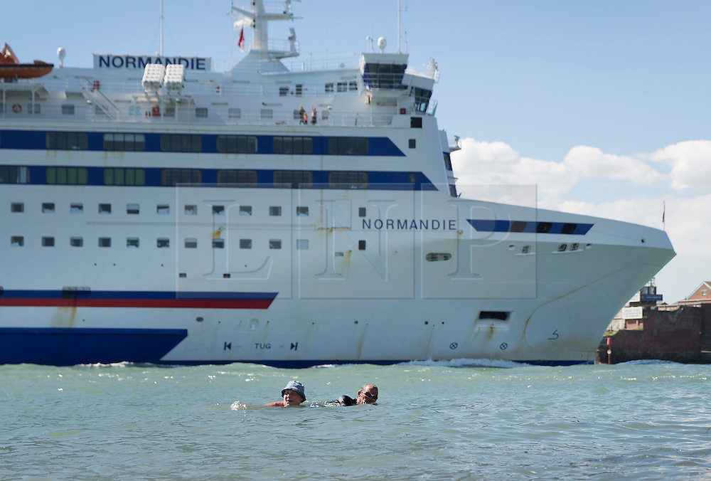 © Licensed to London News Pictures. 30/08/2016. Portsmouth, UK. Swimmers take to the sea in Old Portsmouth as a Brittany Ferry passes near by. High temperatures are being experiences in parts of the United Kingdom today. Photo credit: Peter Macdiarmid/LNP