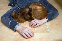 Woman Lying on the floor after being beaten,