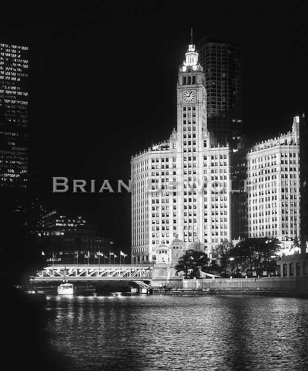 Accent lighting shows the great form and architecture of the Wrigley Building on Michigan Avenue in Chicago. A tour boat is captured as it passes under the Michigan Avenue bridge.