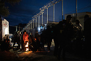 A group a men warming at a fire next to the fence delimitating the official camp from the one bult by Greeke authorities. About 20000 are living in a makeshift camp nearby the city of Moria on the island of Lesbos in miserable conditions, most of the without water, electricity nor sanitary facilities.  Federico Scoppa