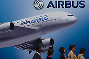 Delegates walk past a billboard of an A380 airliner outside one of the EADS company's chalets at the Farnborough Air Show. The Airbus A380 is a double-deck, wide-body, four-engine jet airliner manufactured by the European corporation Airbus, a subsidiary of EADS. It is the world's largest passenger airliner and, due to its size, many airports have had to expand their facilities to properly accommodate it. The Farnborough International Airshow is a seven-day international trade fair for the aerospace industry and held every two years in mid-July, known as the home of British aviation, held since there since 1948. The show is usually attended by more than 1,300 exhibitors and 150,000 trade visitors.