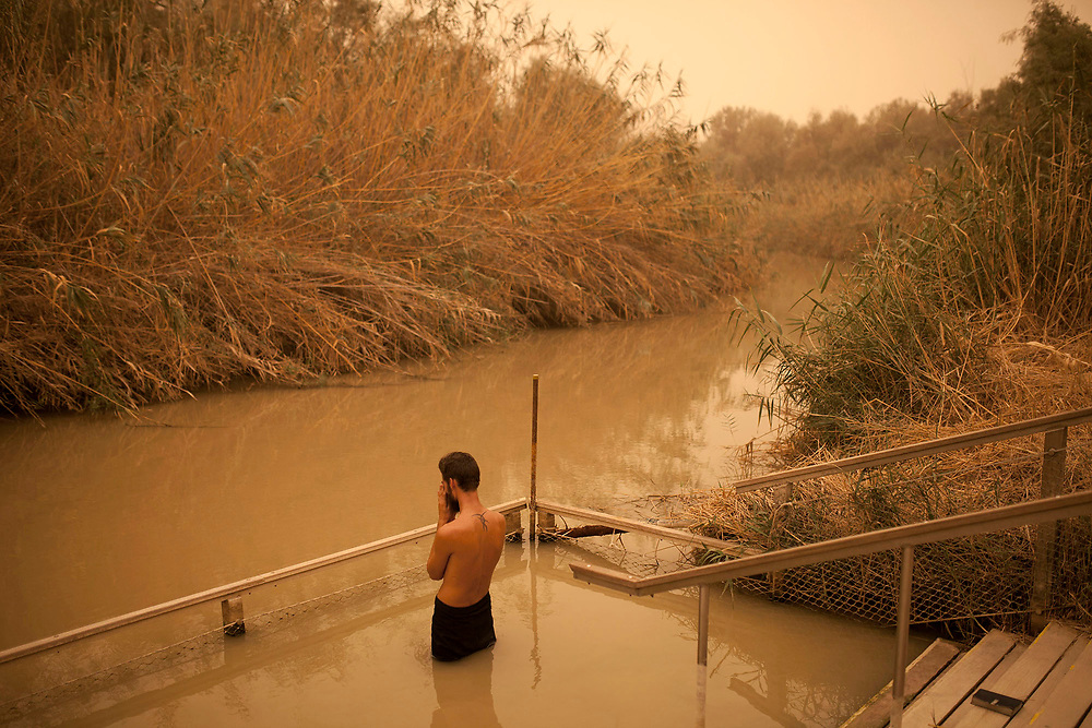 Pilgrim Mateo Black prays in the water of the Jordan River, at the Quaser El YAhud baptism site on the Israeli Jordanian border.<br />