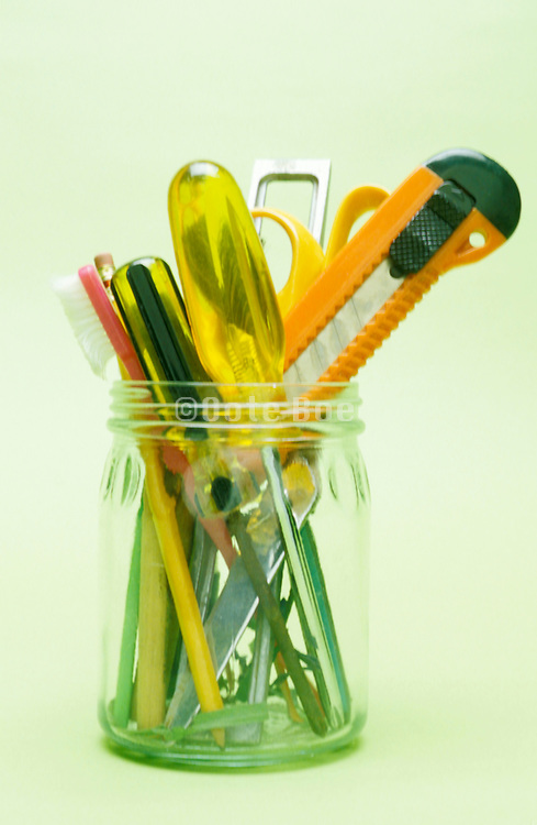 assortment of tools in a glass jar