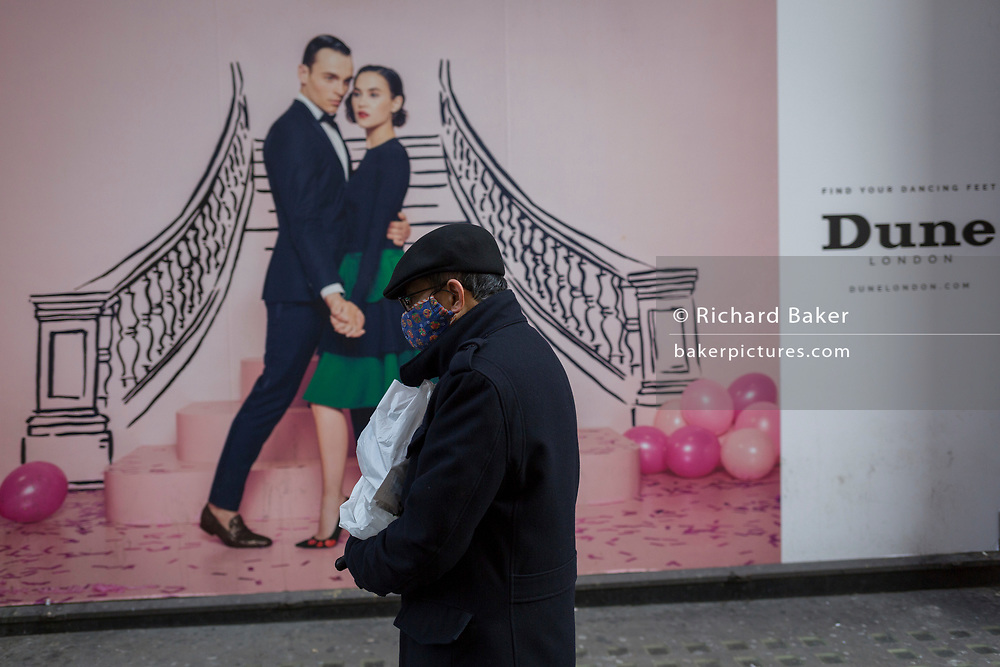 A man wearing a face mask walks past a hoarding for clothing retailer, Dune, on 12th December 2017, in London England.
