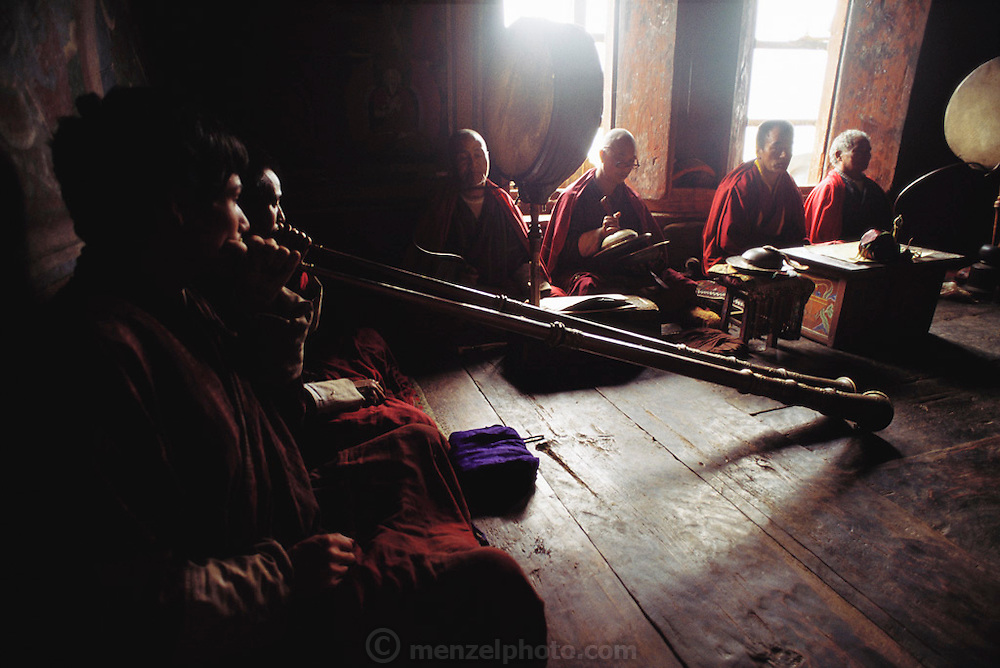 At the Shingkhey village temple in Bhutan, a two-day ceremony is held every year to bless the village. To a continuous background of chanting, the monks fill the valley with long, slow, deep notes from their horns. The drum in the center of the room beats with a deep, resonant, almost ringing sound. Published in Material World: A Global Family Portrait, page 78.