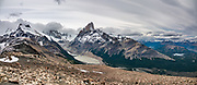 """From Mirador Loma del Pliegue Tumbado, see Cerro Fitz Roy (3405 m or 11,171 ft elevation) rising high above Laguna Torre (634 m or 2080 ft). Clouds hide Cerro Torre. From El Chalten, we hiked to Mirador """"Loma del Pliegue Tumbado"""" (""""hill of the collapsed fold""""), 19 km (11.9 mi) with 1170 meters (3860 ft) cumulative gain in Los Glaciares National Park, in Argentina, Patagonia, South America. El Chalten mountain resort is 220 km north of El Calafate. Chaltén comes from a Tehuelche word meaning """"smoking mountain"""", due to clouds that usually form over Monte Fitz Roy. El Chalten mountain resort is in Santa Cruz Province, Argentina, Patagonia, South America. This image was stitched from multiple overlapping photos."""