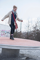 Young woman balancing on playground spinner, Munich, Bavaria, Germany