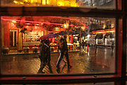 People holding umbrellas walk in Soho, in central London as heavy rain batters the capital on Friday, Oct 2, 2020. Forecasters warn Southern coastal areas of England could see gusts of up to 65mph and others could be at risk of flooding before the end of the weekend, as the French storm arriving on Friday is expected to be followed by another band of cold and blowy conditions. (VXP Photo/ Sabrina Merolla)