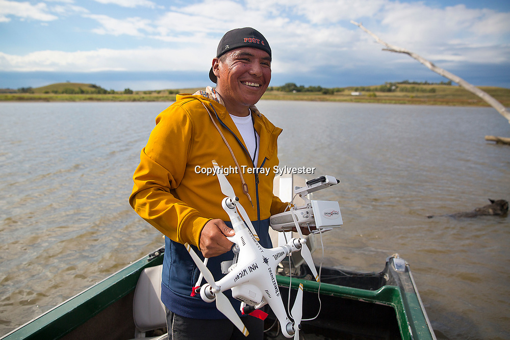 Shiyé Bidzïïl of the Standing Rock Sioux and Navajo tribes poses for a portrait while preparing to launch his drone from the Cannonball River near the route of the Dakota Access oil pipeline on September 8, 2016. Cannon Ball, North Dakota, United States.