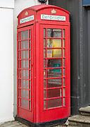 Old red telephone box used for a defibrillator, Saffron Walden, Essex, England, UK
