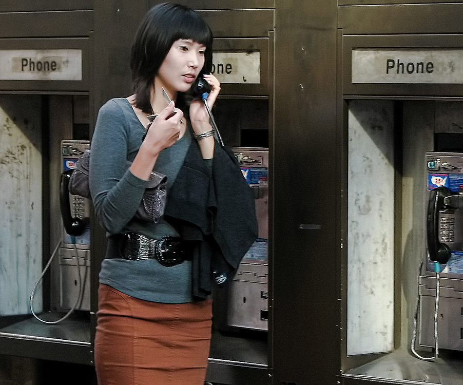 Pretty Asian girl on phone at phone booths. NYC 2007