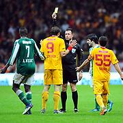Referee's Huseyin GOCEK show the yellow card to Galatasaray's Johan ELMANDER (C) during their Turkish Super League soccer match Galatasaray between Bursaspor at the TT Arena at Seyrantepe in Istanbul Turkey on Sunday 16 October 2011. Photo by TURKPIX
