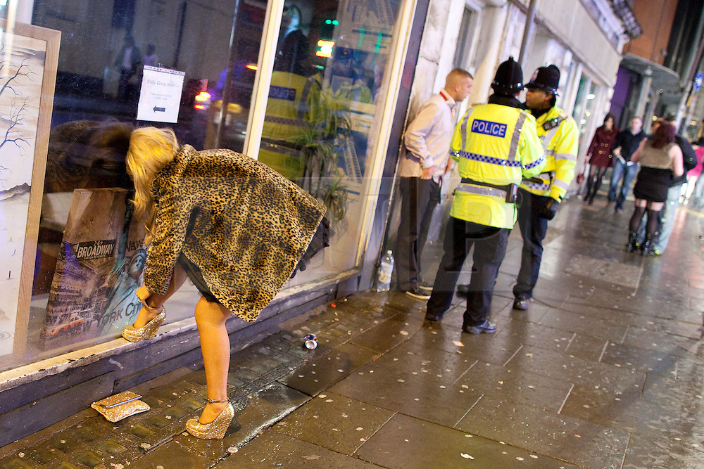 © licensed to London News Pictures. Manchester, UK 01/01/2012. New Years Day revellers in Manchester. A young woman adjusts an ankle bracelet as behind her a man is detained by police. Please see special instructions for usage rates. Photo credit should read Joel Goodman/LNP