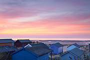 Looking out to a sunset over the wash from amongst Old Hunstanton's delightful collection of beach huts. A dusk scene in North Norfolk, East Anglia.