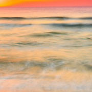 Long exposure captures gentle motion of the Gulf of Mexico at day's end, with soft sunset colors.