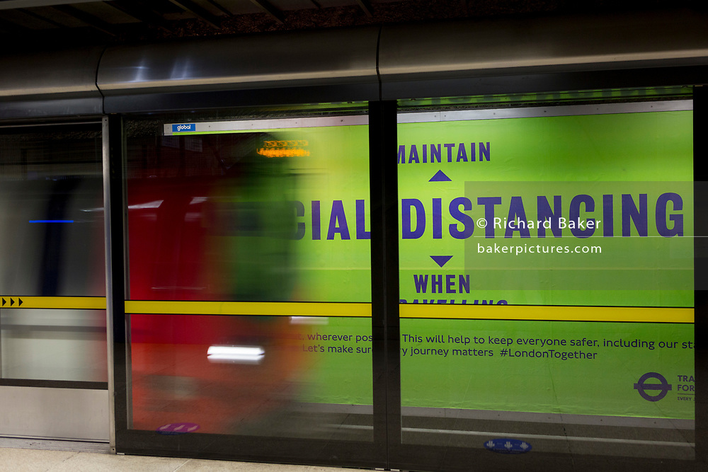 As the UK's Conornavirus pandemic lockdown continues, but with travel restrictions and social distancing rules starting to ease after three months of closures and isolation, a train blurs across a platform banner for social distancing at London Underground's Canary Wharf station, on 9th June 2020, in London, England.