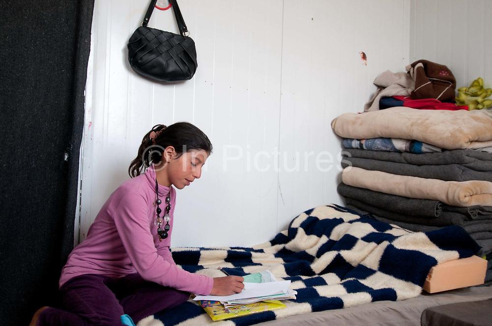 Jordan. Zaatari Camp for Syrian Refugees. Qamar reads her school book.