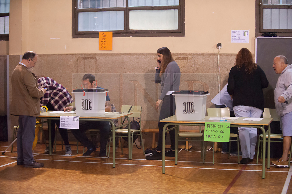 """© Licensed to London News Pictures. 01/10/2017. Barcelona, Spain.  <br /> <br /> Members of the organization setting the Sedeta de Gracia´s Centre Civic poll station up, a while ago.<br /> <br /> Students, their parents, associations and neighbours have organized to carry out """"playful activities"""" during the weekend and keep open the Sedeta de Gracia´s Centre Civic.<br />  <br /> Since early in the morning dozens of people wait at the college´s door for the voting time under the rain.<br /> <br /> Mossos d´Escuadra said they won´t do nothing if that can destabilize social order.<br /> <br /> Catalonia is awaiting for today, October 1st, when the Spanish Region wants to vote in a self-determination referendum to get a independence.<br /> <br /> The Referendum´s Law was passed on last September 6th at the Catalonian Parliament thanks to the votes of """"Junts pel Sí"""" and """"CUP"""". Then it was suspended by the Spanish Constitutional Court, on next day.<br /> Carles Puigdemont, the President of the Government ofCatalonia, said he would ignore that and he and his Government will continue with the Referendum.<br /> <br /> The Spanish Government has sent to Catalonia thousands of """"Guardia Civil"""" and """"Policía Nacional"""" officers (two of the Spanish forces and state security forces), to enforce the ruling of the Constitutional Court and avoid the voting process on next Sunday. They will work with the Mossos d´Escuadra (the Autonomic police in Catalonia).<br /> <br /> To avoid the vote, the Spanish Government has prevented the opening of polling stations, some of which are schools.  <br /> <br /> Photo credit: Gustavo Valiente/LNP"""