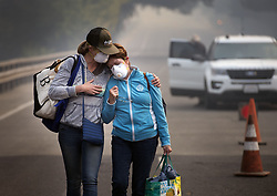 October 11, 2017 - Napa, California, U.S. - COLBY CLARK of San Francisco, left, comforts her mother, BONNIE TREXLER, after being escorted by law enforcement to her home in Silverado Highland to retrieve medicine and some personal items on Wednesday. Trexler was one of the lucky few who found that her home was spared from the devastating fire which burned homes around her Monday. (Credit Image: © Randy Pench/Sacramento Bee via ZUMA Wire)