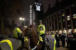 © Licensed to London News Pictures. 01/01/2021. London, UK. Mounted police attempt to disperse crowds gathering on New Year's Eve as Big Ben strikes midnight near Parliament in central London. Photo credit: Peter Macdiarmid/LNP